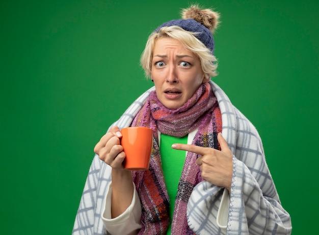 Kranke ungesunde frau mit kurzen haaren in warmem schal und hut, die sich unwohl eingewickelt fühlen, verwirrt in blankebeing verwirrtes halten der tasse tee, der mit index fignerat zeigt, der über grünem hintergrund steht