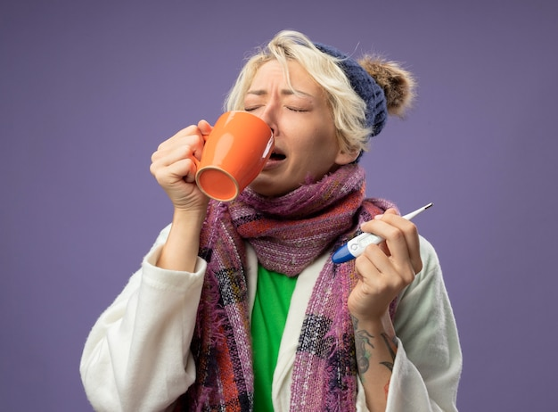 Kranke ungesunde frau mit kurzen haaren in warmem schal und hut, die sich unwohl fühlen, halten tasse heißen tee und thermometer, die tee trinken, der über lila wand steht