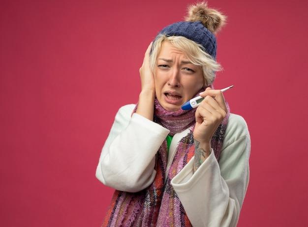 Kranke ungesunde frau mit kurzen haaren in warmem schal und hut, die sich unwohl fühlen, halten thermometer baing in der panik, die über rosa wand steht