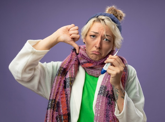 Kranke ungesunde frau mit kurzen haaren in warmem schal und hut, die sich unwohl fühlen, zeigt thermometer mit unglücklichem gesicht, das daumen unten zeigt, die über lila wand stehen
