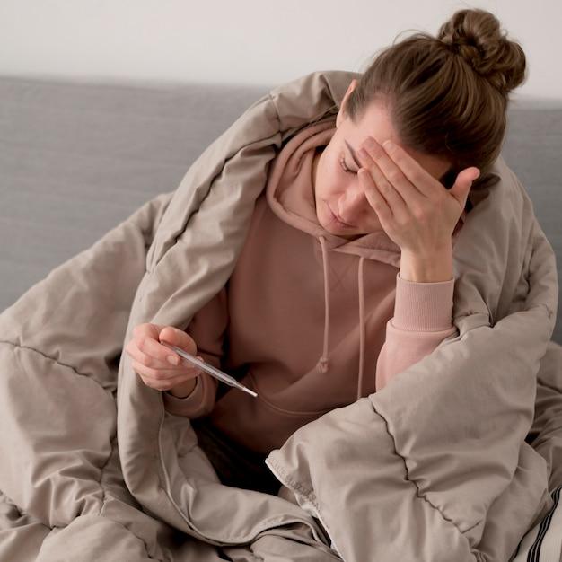 Kranke weibliche person, die das thermometer betrachtet