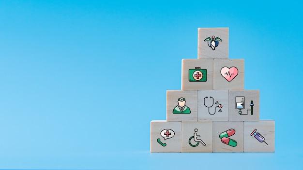 Kranken- und krankenversicherungssymbol auf holzwürfelstapel als pyramidenform, krankenhausgesundheitskonzept