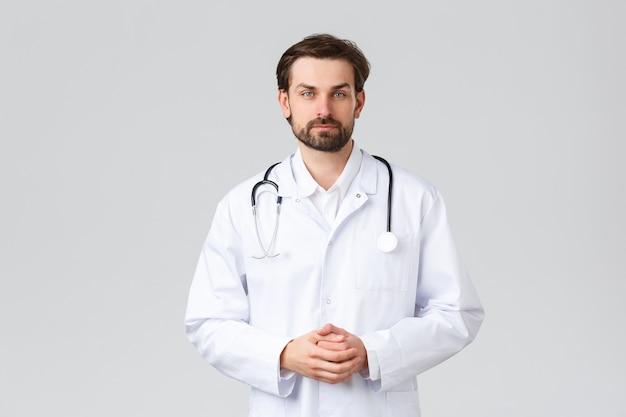 Krankenhaus, gesundheitspersonal, covid-19-behandlungskonzept. junger arzt in peelings, der tägliche besorgungen in der klinik macht, auf die symptome des patienten hört, in die kamera schaut, ein professioneller arzt, der krankheiten heilt