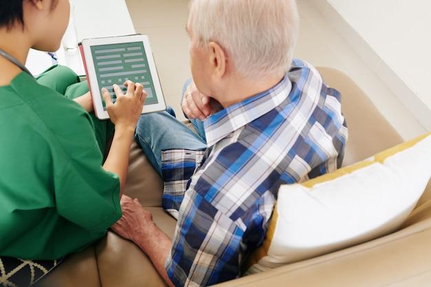 Krankenhausangestellter hilft beim ausfüllen des versicherungsantragsformulars mit dem patienten