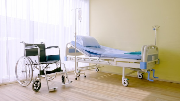 Krankenhausbett und rollstuhl im krankenzimmer.