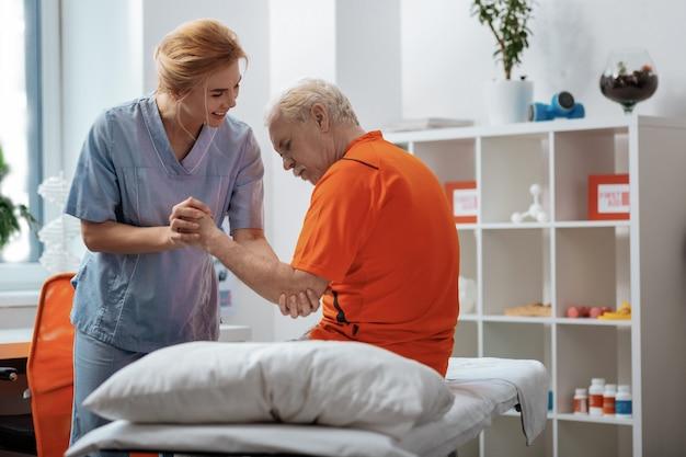 Krankenhauspersonal. ernster alter mann, der auf dem medizinischen bett sitzt, während er von einer krankenschwester unterstützt wird