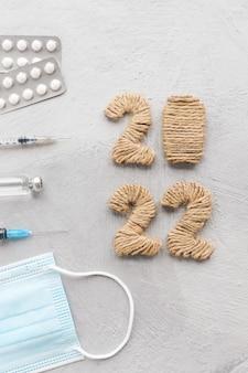 Krankenkarte mit arztausrüstung und nummern 2022, die auf einer grauen tischplattenansicht liegen