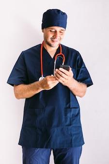 Krankenpfleger, arzt oder tierarzt in blauer uniform an einem fenster in einem krankenhaus mit blick auf das handy. medizin-, krankenhaus- und gesundheitskonzept.
