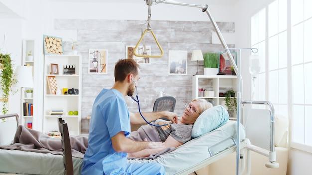 Krankenpfleger, der die herzschläge einer kranken alten dame überprüft, die im krankenhausbett in einem hellen und gemütlichen pflegeheim liegt
