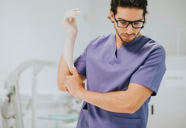 Krankenpfleger zieht einen handschuh an