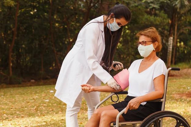Krankenschwester arzt, der den druck der älteren frau misst