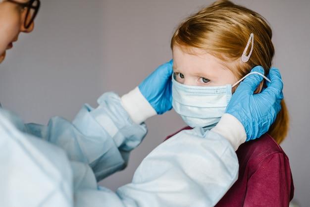 Krankenschwester, arzt in einem schutzanzug, trägt eine medizinische maske im gesicht für das kind. vorbeugende maßnahmen gegen covid-19-infektion. konzept des schutzes gegen influenza, corona-virus-epidemie.