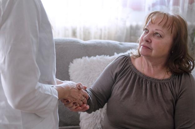 Krankenschwester begrüßt eine alte frau mit einem händedruck