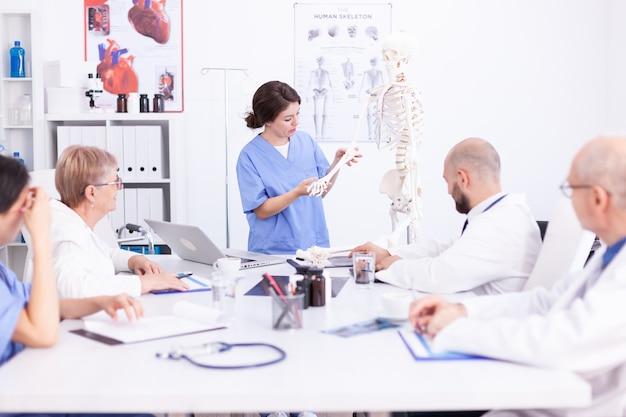 Krankenschwester demonstriert am skelett vor ärzten im konferenzraum. klinik-expertentherapeut im gespräch mit kollegen über krankheit, mediziner