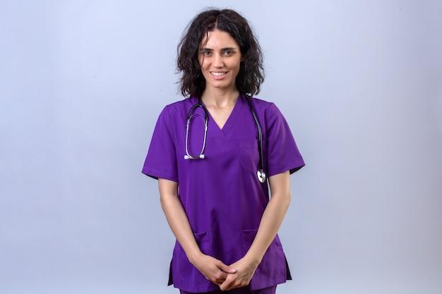 Krankenschwester der jungen frau in der medizinischen uniform und im stethoskop stehend mit dem selbstbewussten lächeln, das schaut