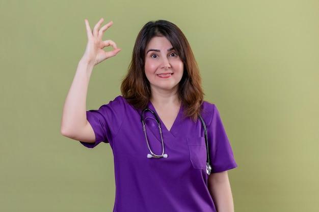 Krankenschwester des mittleren alters, die medizinische uniform trägt und mit stethoskop betrachtet kamera, die fröhlich tut, ok zeichen zu tun, das über lokalisiertem grünem hintergrund steht