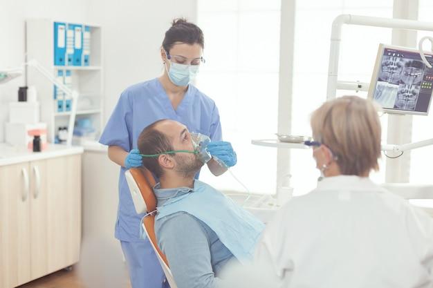 Krankenschwester des stomatologen, die dem patienten, der zahnschmerzen untersucht, eine sauerstoffmaske aufsetzt