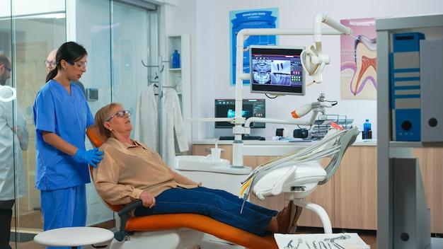 Krankenschwester, die ältere frau in konsultationszahnzimmer einlädt, während der arzt mit dem patienten spricht. assistent im gespräch mit älteren patienten, die sich auf die stomatologische untersuchung vorbereiten. professionelle ortho