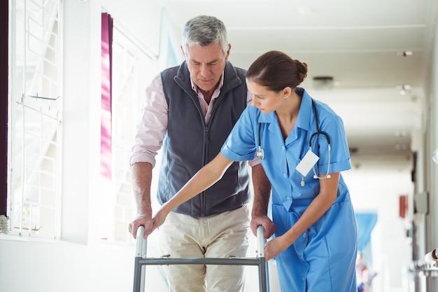 Krankenschwester, die älteren mann mit gehhilfe hilft