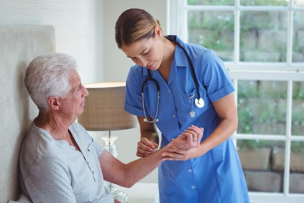 Krankenschwester, die älteren mann überprüft