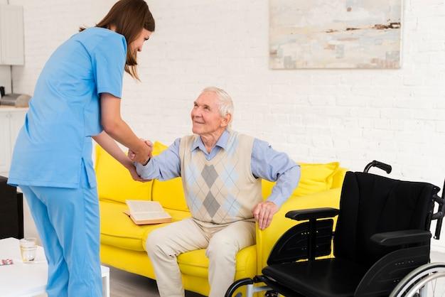 Krankenschwester, die altem mann hilft aufzustehen