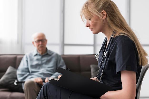 Krankenschwester, die alten mann in einem pflegeheim berät
