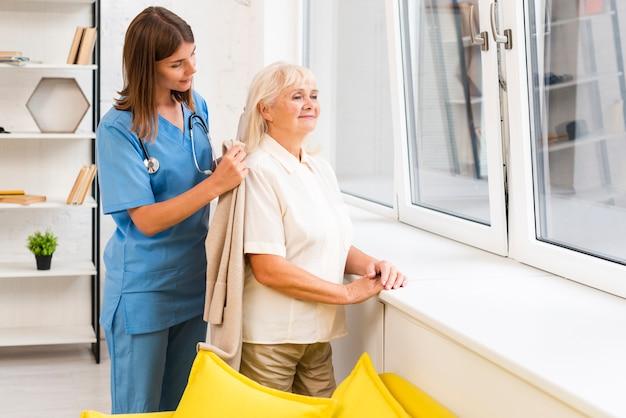 Krankenschwester, die alter frau mit ihrem mantel hilft