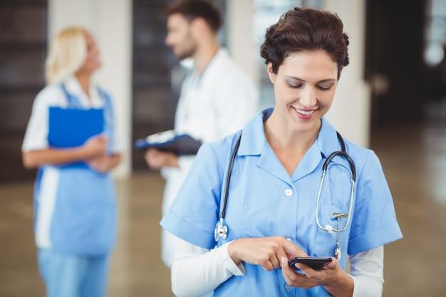 Krankenschwester, die am handy verwendet