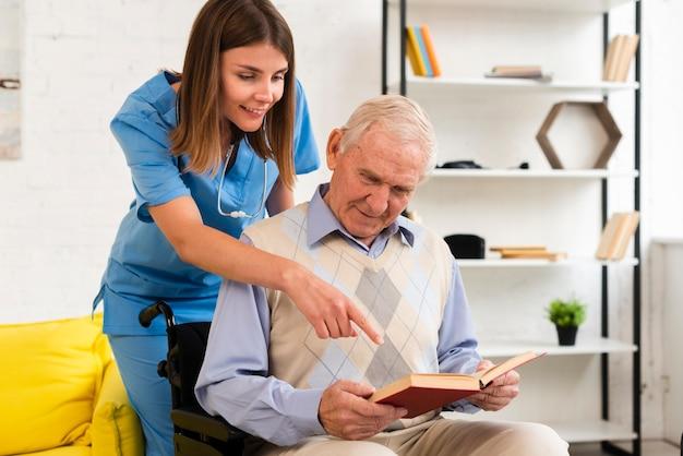 Krankenschwester, die auf das buch des alten mannes zeigt