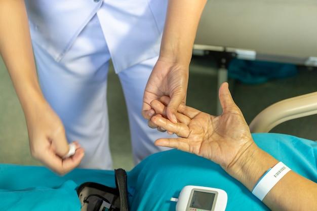Krankenschwester, die blutzuckerspiegel patoent mit glucometer im krankenhaus überprüft.