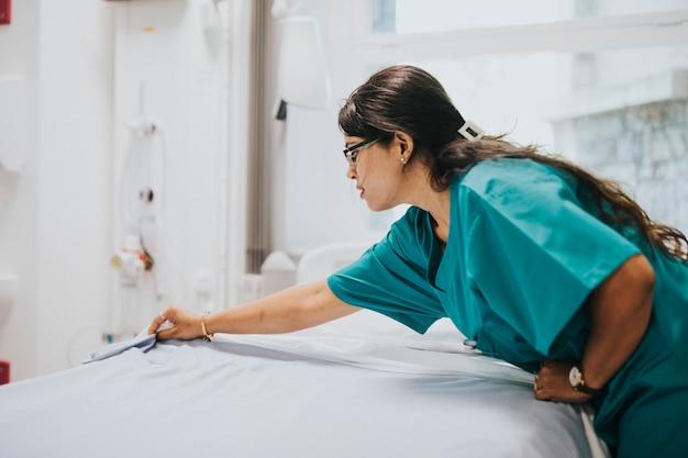 Krankenschwester, die das bett in einem krankenhaus macht