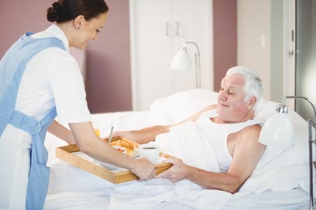 Krankenschwester, die dem älteren mann das frühstück liegt auf bett gibt