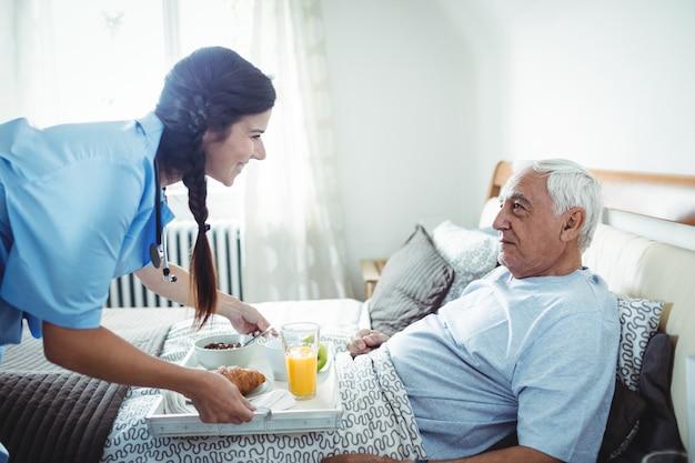 Krankenschwester, die dem älteren mann das frühstück serviert