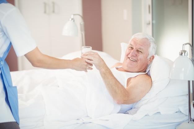 Krankenschwester, die dem älteren mann wasserglas gibt