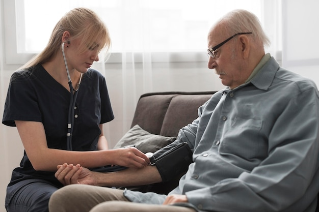 Krankenschwester, die den blutdruck des älteren mannes überprüft