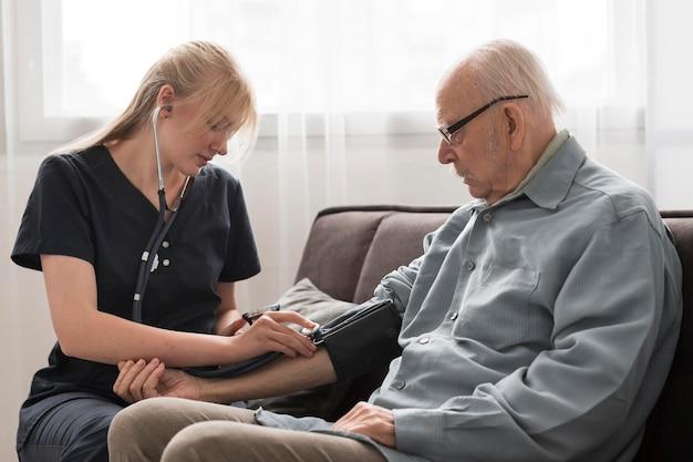 Krankenschwester, die den blutdruck des alten mannes überprüft