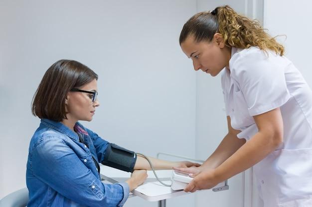 Krankenschwester, die den blutdruck des weiblichen patienten im büro nimmt