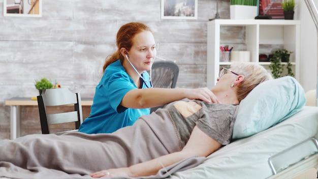 Krankenschwester, die den herzschlägen der alten dame zuhört. sie liegt in einem krankenhausbett in einem hellen, gemütlichen pflegeheim