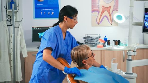 Krankenschwester, die den patienten vorbereitet, der ein zahnmedizinisches lätzchen anordnet, während der arzt auf den monitor zeigt. kieferorthopäde-spezialist im gespräch mit älterer frau, zahnarzt und krankenschwester, die in einer modernen klinik zusammenarbeiten