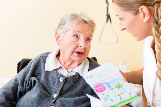 Krankenschwester, die der älteren frau im haus glückwunschkarte gibt