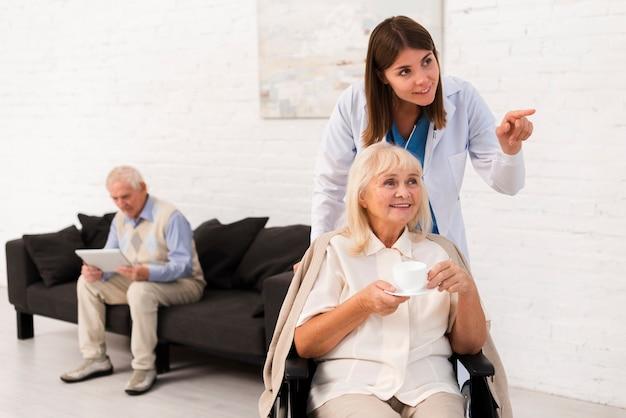 Krankenschwester, die der alten frau etwas zeigt