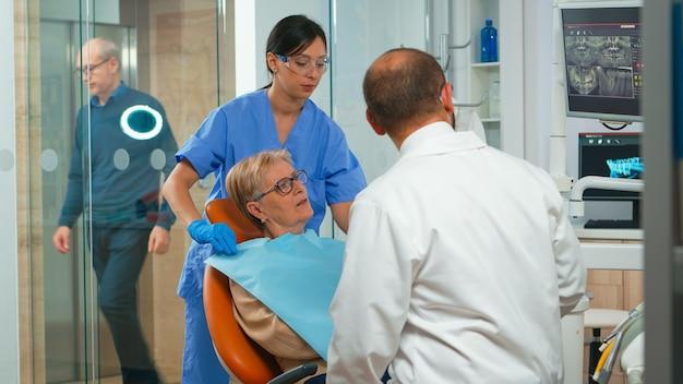 Krankenschwester, die der alten frau während der stomatologischen untersuchung ein zahnmedizinisches lätzchen anlegt. arzt und krankenschwester arbeiten in einer modernen kieferorthopädischen klinik zusammen und zeigen röntgenaufnahmen von zähnen auf dem monitor, der auf digitalen bildschirm zeigt