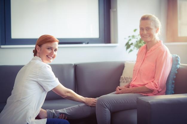 Krankenschwester, die der frau beinmassage gibt