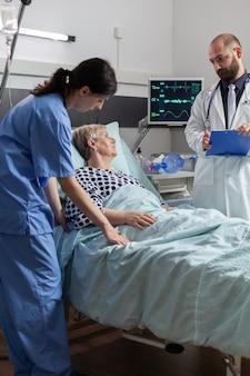 Krankenschwester, die die blutsauerstoffsättigung von einem oxymeter-gerät liest, das an einer kranken älteren patientin befestigt ist, die im krankenhausbett ruht. arzt überwacht den gesundheitszustand des patienten.
