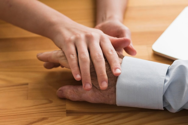 Krankenschwester, die die hand des alten mannes in einem pflegeheim hält