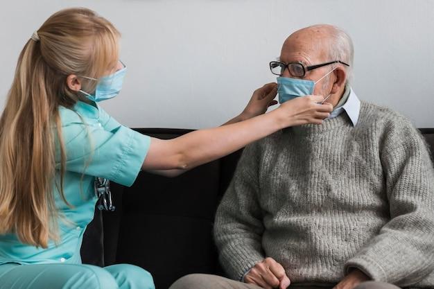 Krankenschwester, die die medizinische maske des alten mannes anpasst