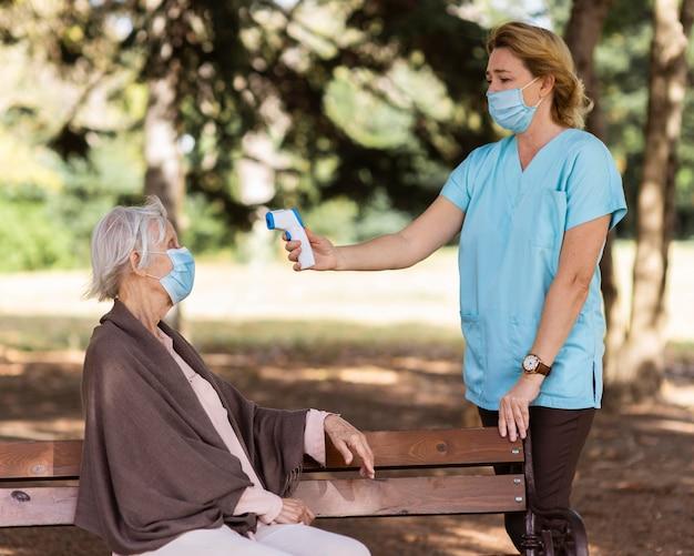 Krankenschwester, die die temperatur der älteren frau draußen auf einer bank prüft