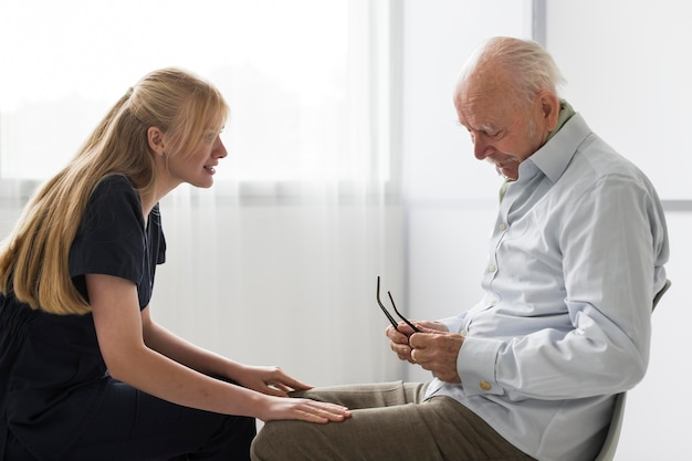 Krankenschwester, die ein gespräch mit altem mann in einem pflegeheim hat