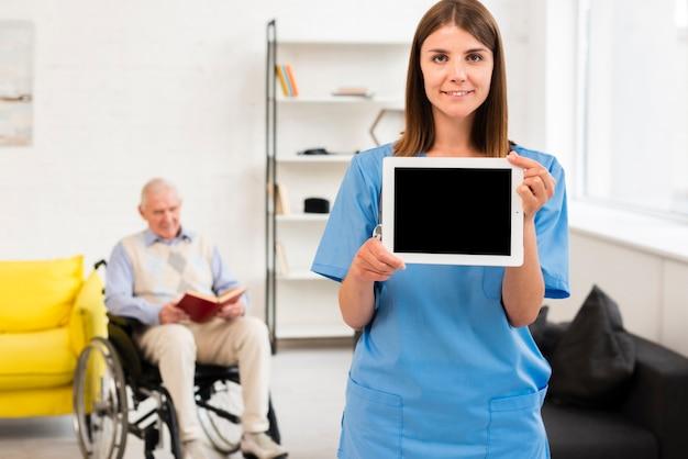 Krankenschwester, die ein tablettenmodell hält