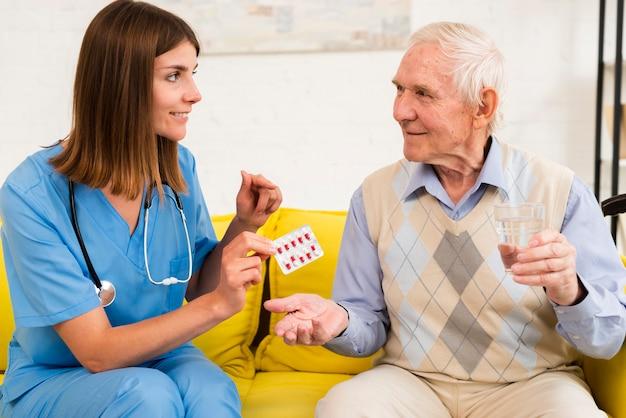 Krankenschwester, die einem alten mann seine pillen gibt